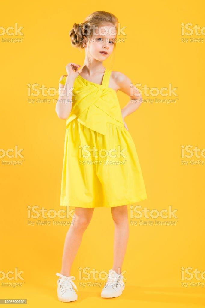 La chica rubia Coloque una mano en su cadera y la otra sostiene el hombro. - foto de stock