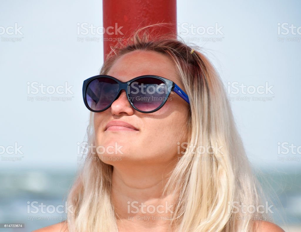 7381357c419 The blonde in sunglasses on beach. Girl resting on beach - Stock image .