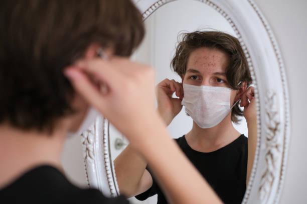 de blonde tienerjongen draagt hygenic masker in de pandemie van het coronavirus - mirror mask stockfoto's en -beelden