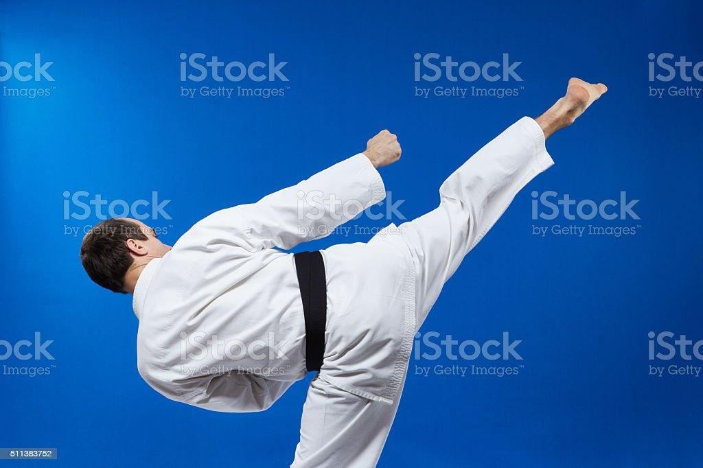 The blow roundhouse beats athlete in karategi stock photo
