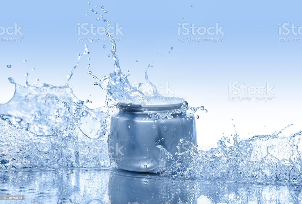 The blue jar of moisturizing cream in the big water splashes stock photo