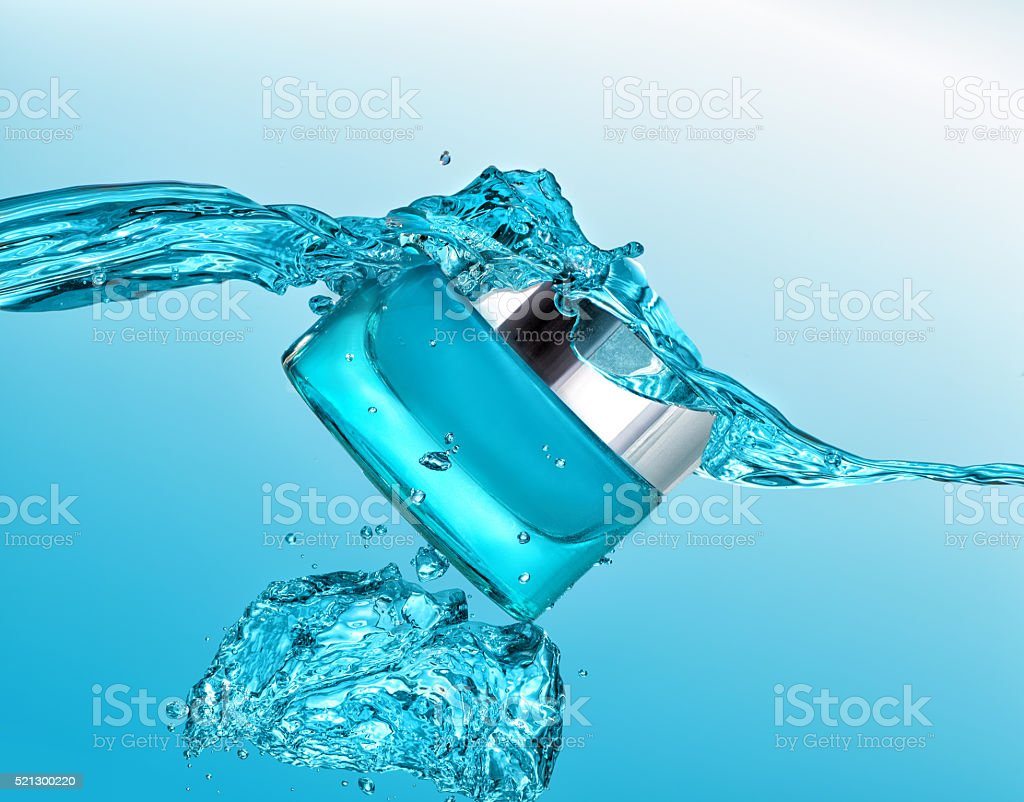 The blue jar of moisturizing cream in the blue water wave stock photo