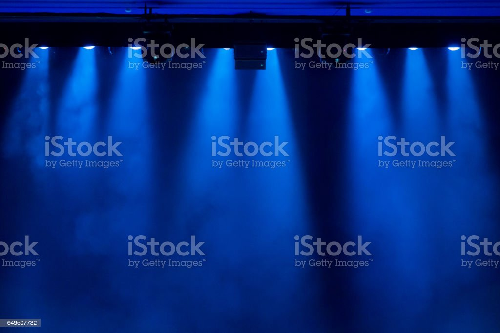 The blue light from the spotlights through the smoke in the theatre during the performance. Lighting equipment. stock photo