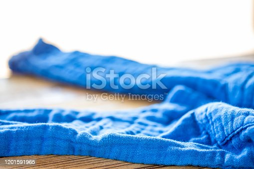 845555910 istock photo The blue pants thrown off on the wooden table. 1201591965