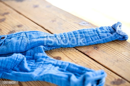 845555910 istock photo The blue pants thrown off on the wooden table. 1201592311