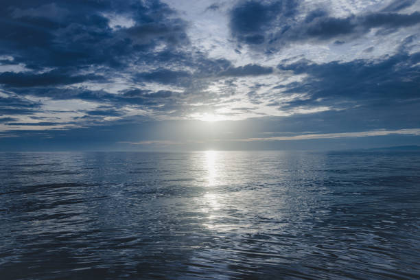 The blue sea and the calm morning sun are shining Photograph of morning sea horizon over land stock pictures, royalty-free photos & images