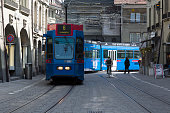 Bern, Switzerland - April 20, 2017: The blue tram turns from one street to the other in the old town. Along the tracks a cyclist and other people can be seen. This is one of the countless wonderful places in Switzerland, which is a tourist attraction often visited by many tourists from all over the world.
