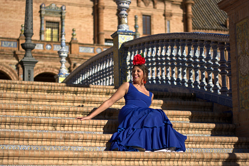 istock The blue-flamenco dress girl sitting on the stairs of Plaza de Espana in Seville, Spain 930187444