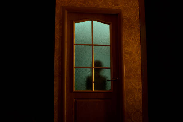 The blurred silhouette of the unknown behind the glass door. stock photo