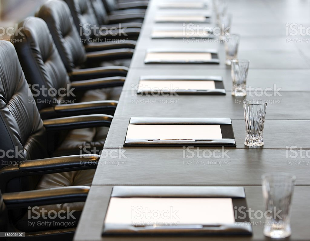 The boardroom table is set for a meeting stock photo