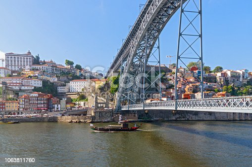 The boat floats on the river Douro under the bridge Dom Luis I Bridge. Scenic view of Ribeira from Vila Nova de Gaia. Porto, Portugal on the summer sunny day.  Travel photography.