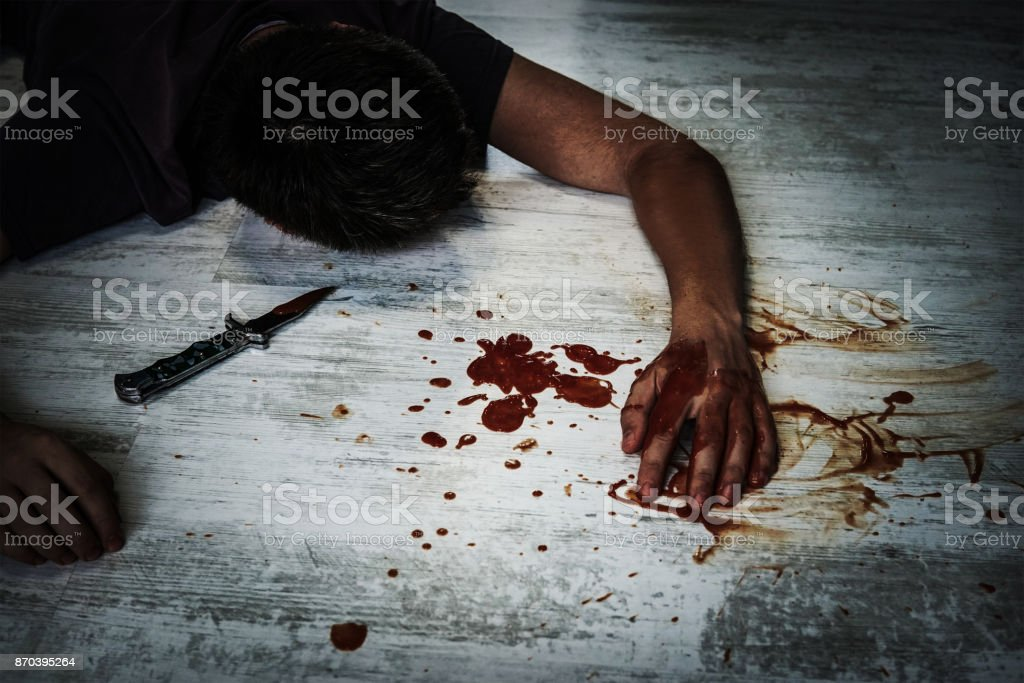 the body of a young man lying on the floor stock photo