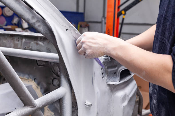 The body repairman grinds the white car's frame with purple emery paper in preparation for painting after applying putty in a vehicle repair workshop and auto service, dust crumbles down. stock photo