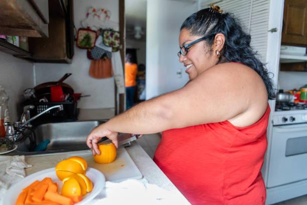 Die körperpositive schöne mexikanisch-amerikanische Frau macht Obstsalat in der heimischen Küche – Foto