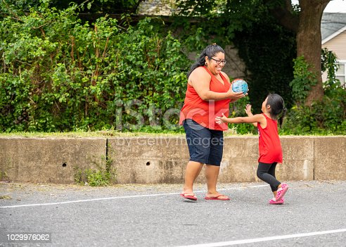 istock The body-positive, cheerful happy Latino, Mexican-American woman playing ball outdoor with her little daughter 1029976062