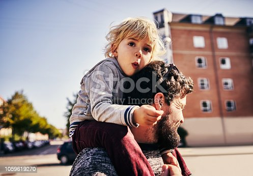 Cropped shot of a young man piggybacking his adorable little son through the city