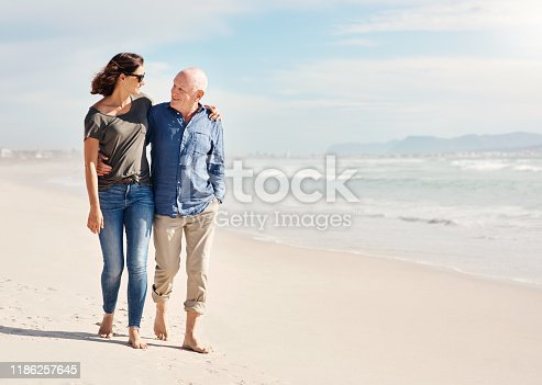 Shot of a young woman going for a walk along the beach with her elderly father