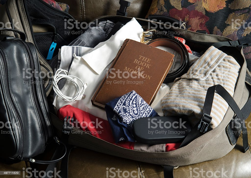 The Book of Mormon in packed mans suitcase stock photo