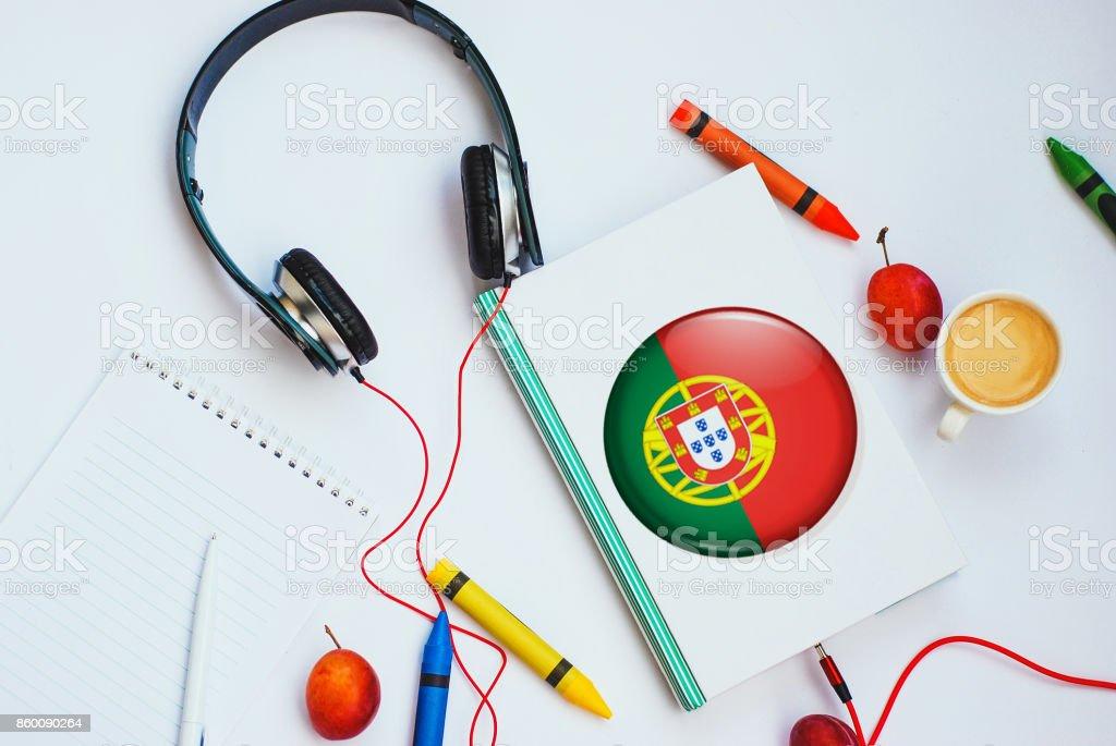 o livro com a bandeira portuguesa e fones de ouvido. conceito de aprendizagem português através de cursos de áudio - foto de acervo