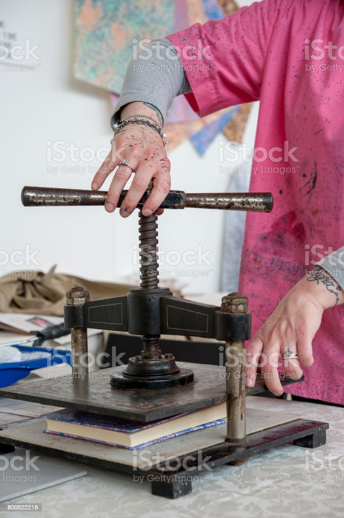 The bookbinder at the hand press stock photo