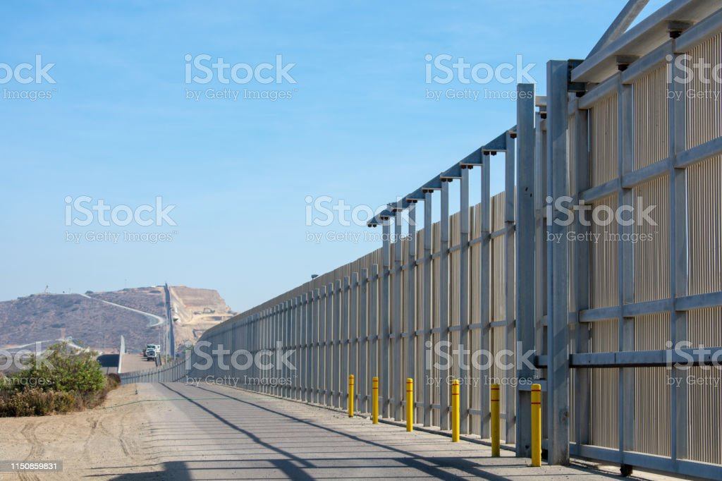 The border wall on the United States - Mexico international border The border wall on the United States - Mexico international border near San Diego in California under blue sky Barricade Stock Photo