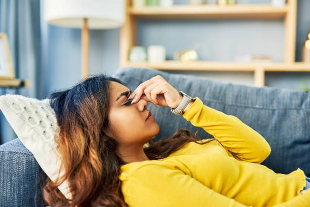 The boredom is giving me a headache Shot of a young woman experiencing a bad headache while relaxing at home headache stock pictures, royalty-free photos & images