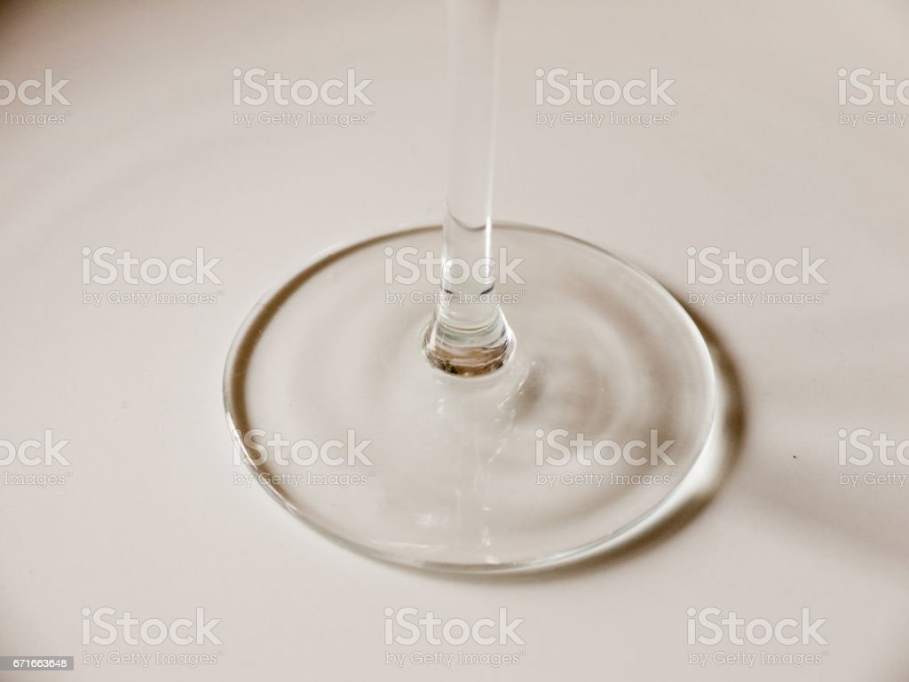The Bottle of A Wine Glass Looking Like Liquid Being Poored onto a White Background Plate Casting Circle Shadows and Making an Interesting Pattern of Glass Ripples stock photo