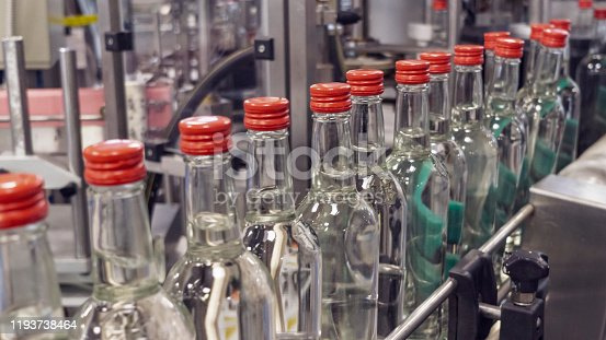 The bottles on the conveyor belt at the plant for bottling of alcoholic beverages, Russian vodka