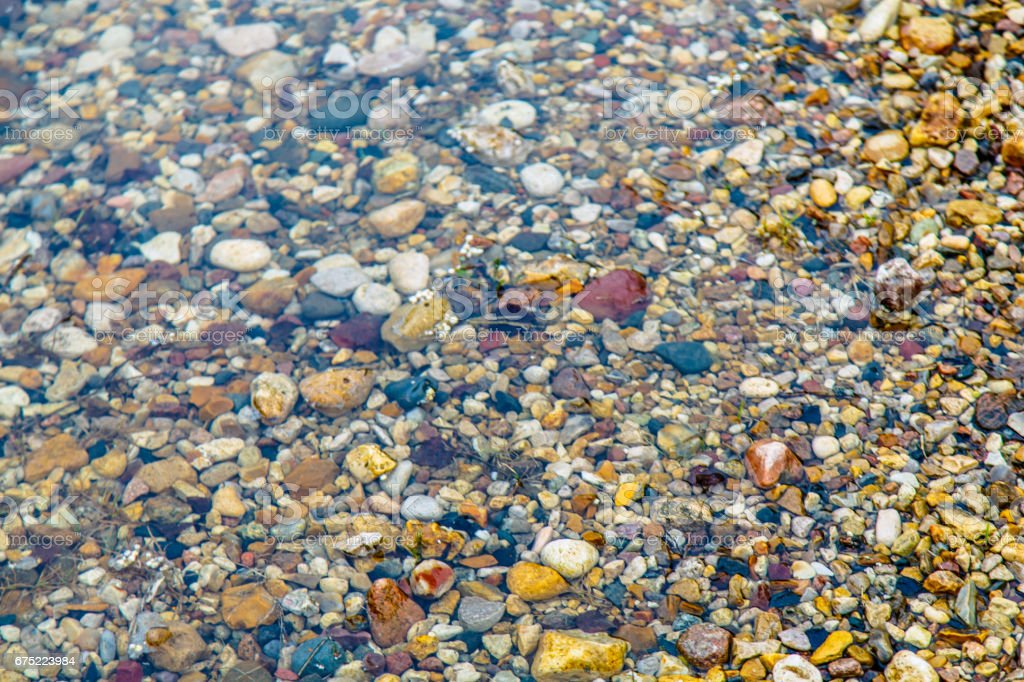 The bottom of colored pebbles in a shallow puddle. royalty-free stock photo