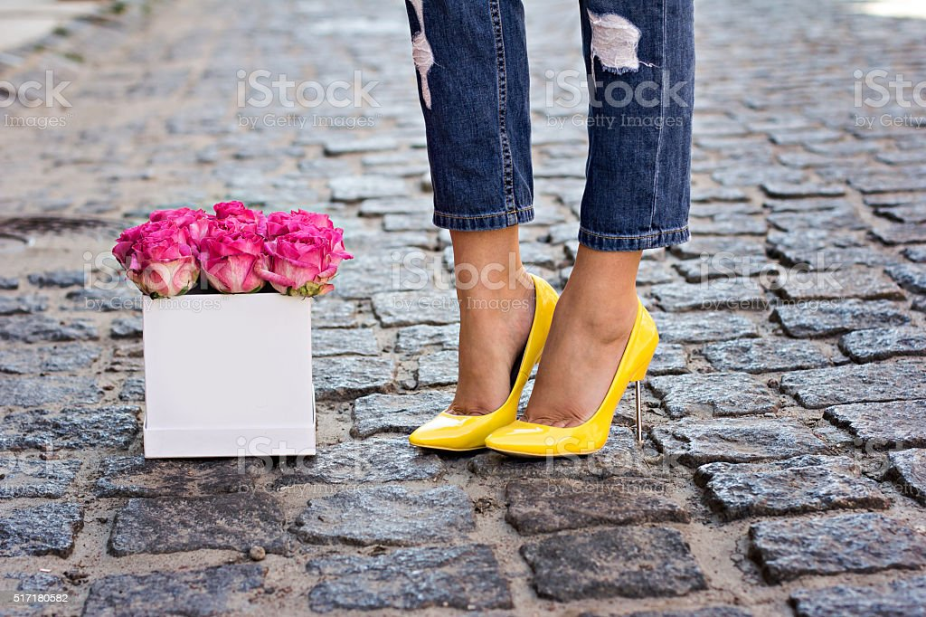 The bouquet of red roses and female legs in jeans stock photo