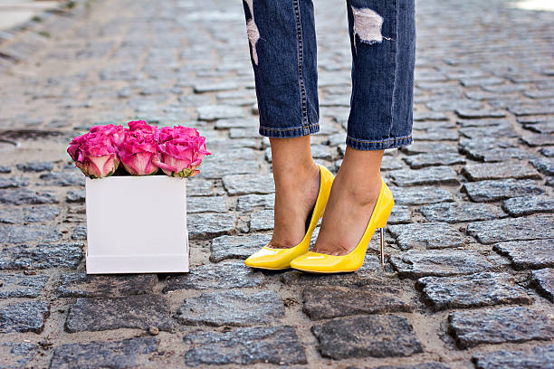 the bouquet of red roses and female legs in jeans - hoge hakken stockfoto's en -beelden