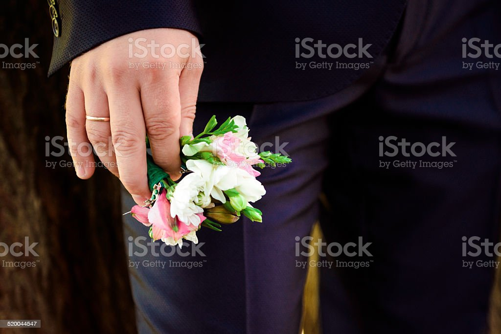 The boutonnière in the hand stock photo