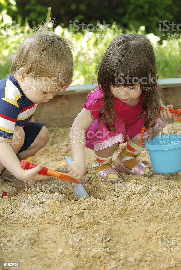 The boy and girl playing to a sandbox stock photo