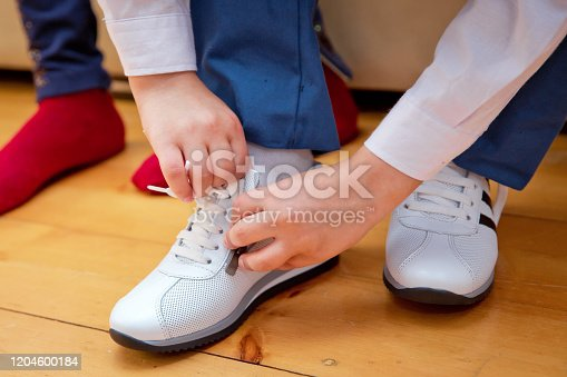 Closes the children's shoes. The boy closes his white shoe garden. close up photo of a boy's legs in white leather child shoes on wooden background