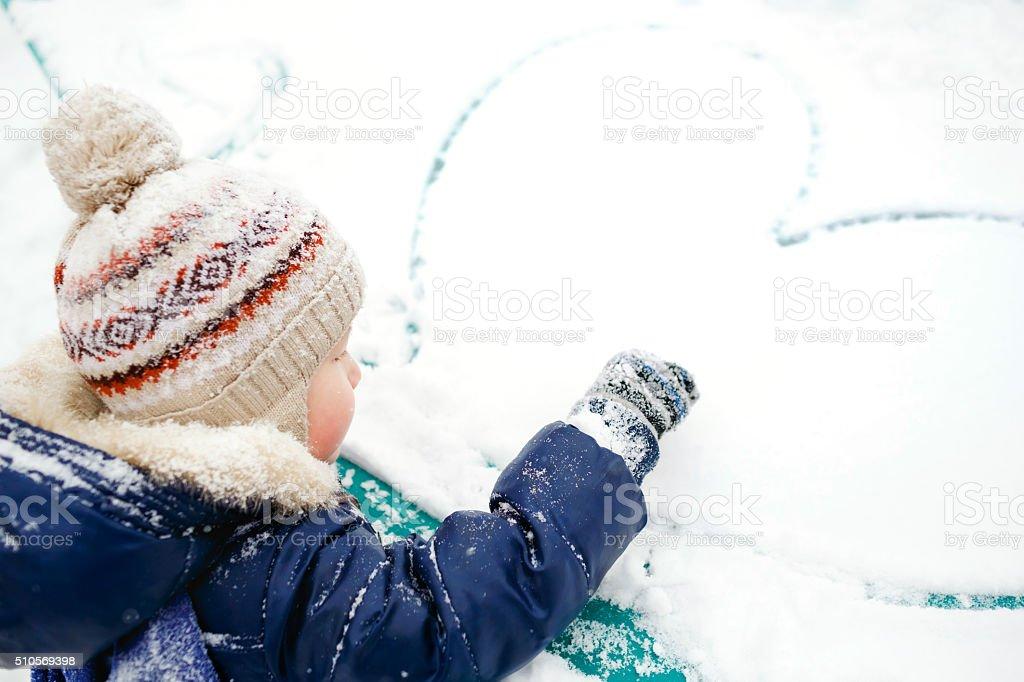 The boy draws heart on snow. Outdoor. Winter, love, friendship stock photo