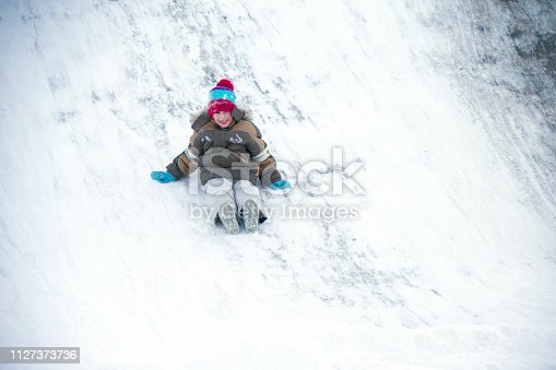 The boy drives off a snow slide