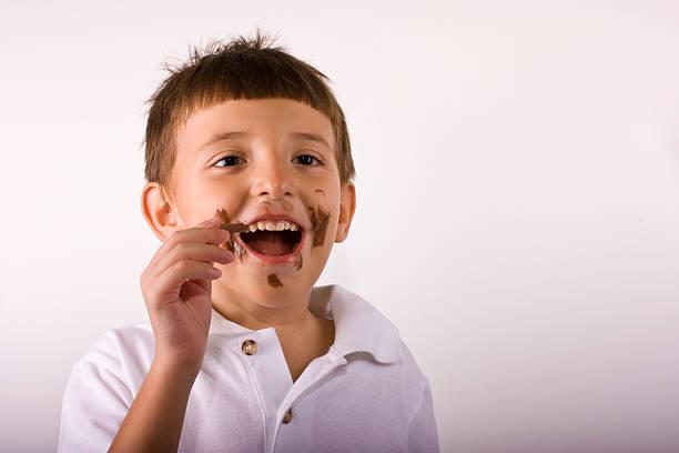 The boy eating chocolate stock photo