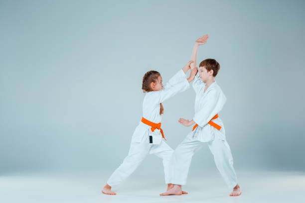 The boy fighting at Aikido training in martial arts school. Healthy lifestyle and sports concept stock photo