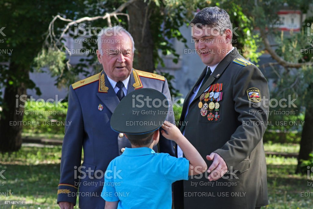 The boy in the cap saluting seniors in rank on Victory day in Volgograd stock photo