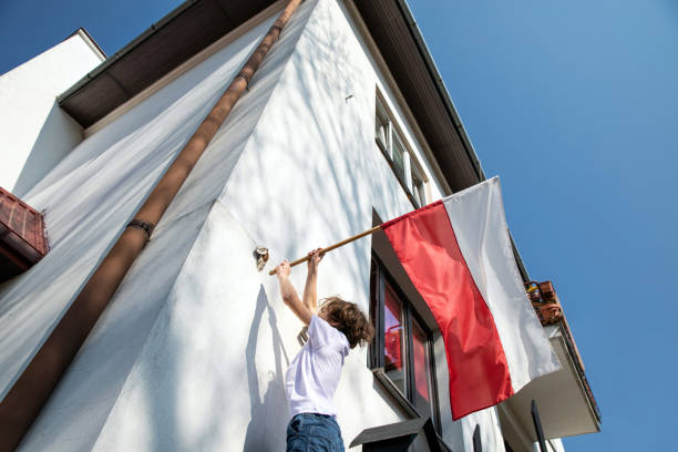 The boy is hanging a flag. Polish National Day of the Third of May, Constitution Day – zdjęcie
