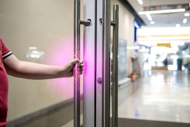de jongen opent de deur naar het winkelcentrum waar een virus of bacterie vastzit aan de deurklink. - pathogeen stockfoto's en -beelden