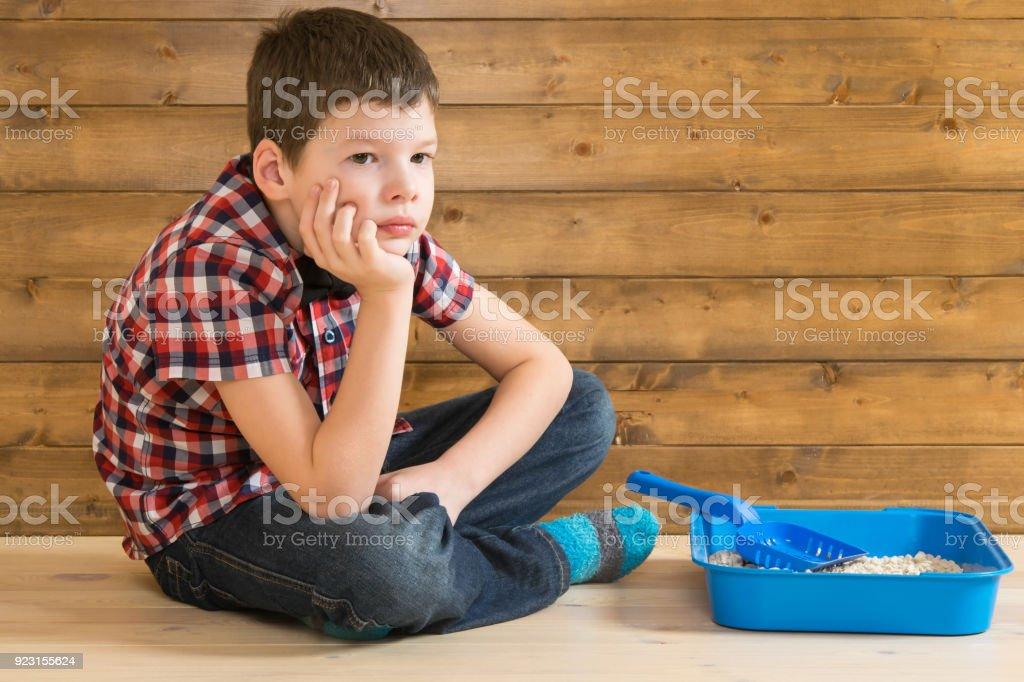 o rapaz está sentado no banheiro para gatinhos e acha que, no contexto de uma parede de madeira - foto de acervo