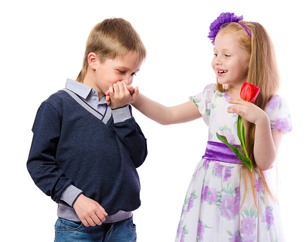 the boy kisses the hand of the girl isolated on white background - little girls little boys kissing love stock photos and pictures