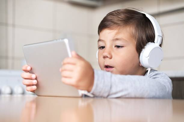 the boy looks at the tablet with interest and plays the game stock photo
