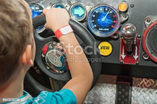 istock The boy on the car simulator 694329236