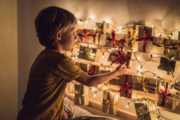 le garçon ouvre un cadeau du calendrier de l'avent - calendrier de l'avent photos et images de collection