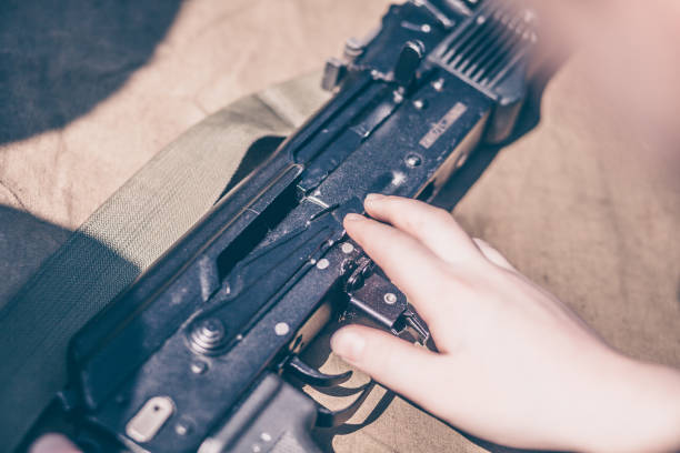 The boy performs disassembly, cleaning and assembly of automatic rifle stock photo