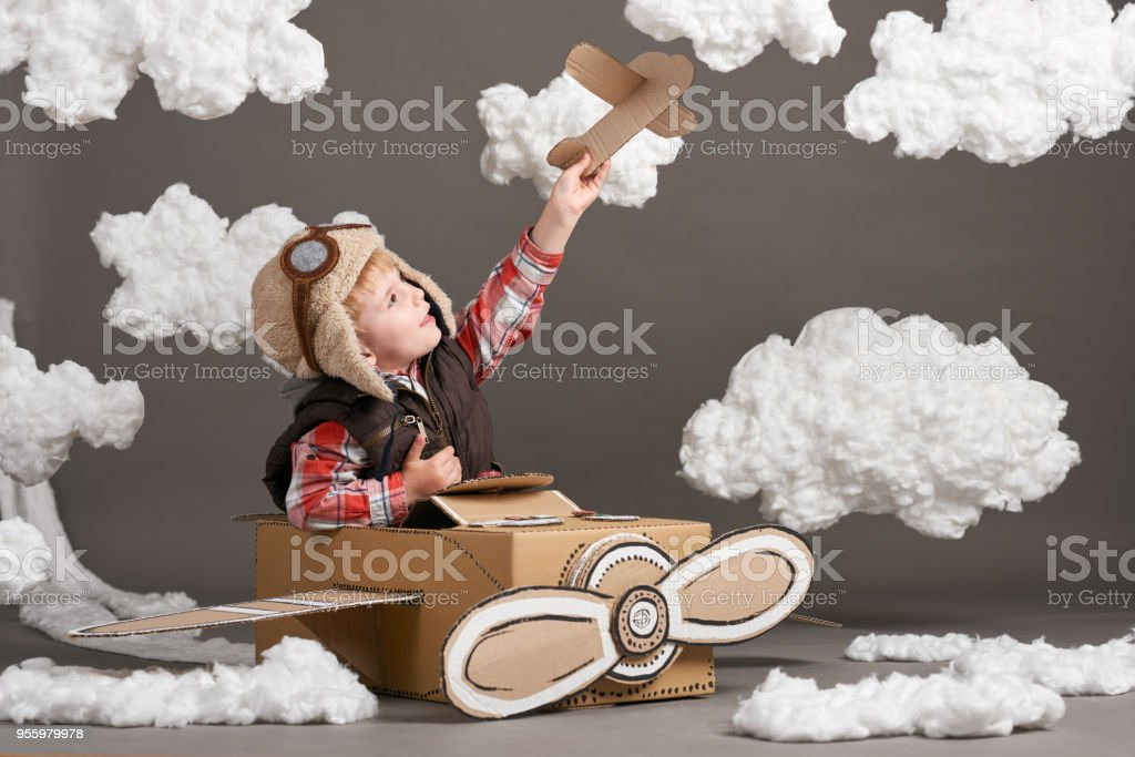 the boy plays in an airplane made of cardboard box and dreams of becoming a pilot, clouds of cotton wool on a gray background stock photo
