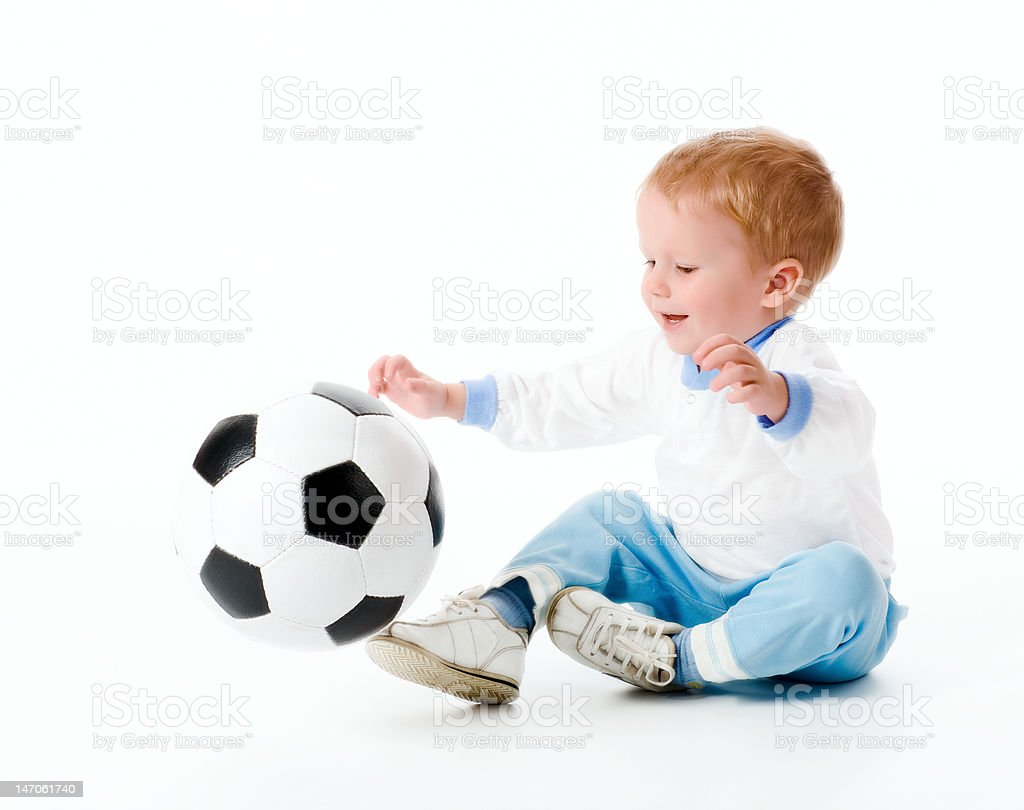 The boy plays with a football stock photo