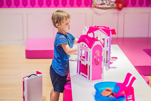 The boy plays with girl toys and dolls.